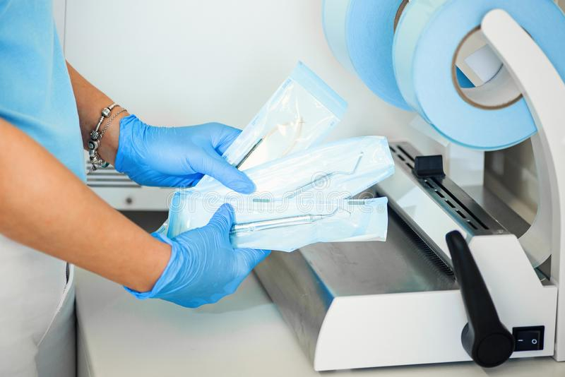Dentist assistant`s hands holding packaged with vacuum packing machine medical instruments ready for sterilizing in. Close up dentist assistant`s hands holding stock images