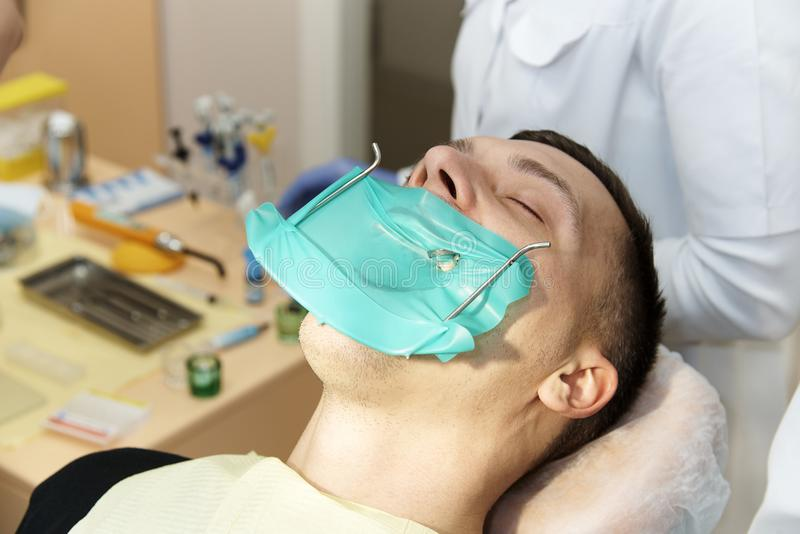 A dentist with a assistants in dental practice stock image