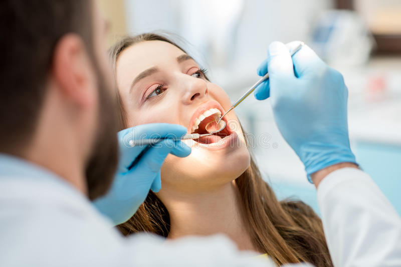 Dentist checking patient teeth stock photo
