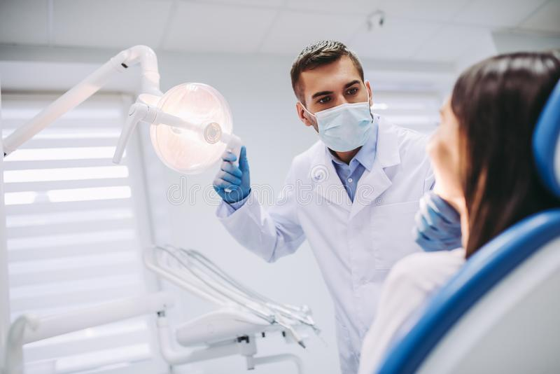 Dentist checking patient teeth stock images