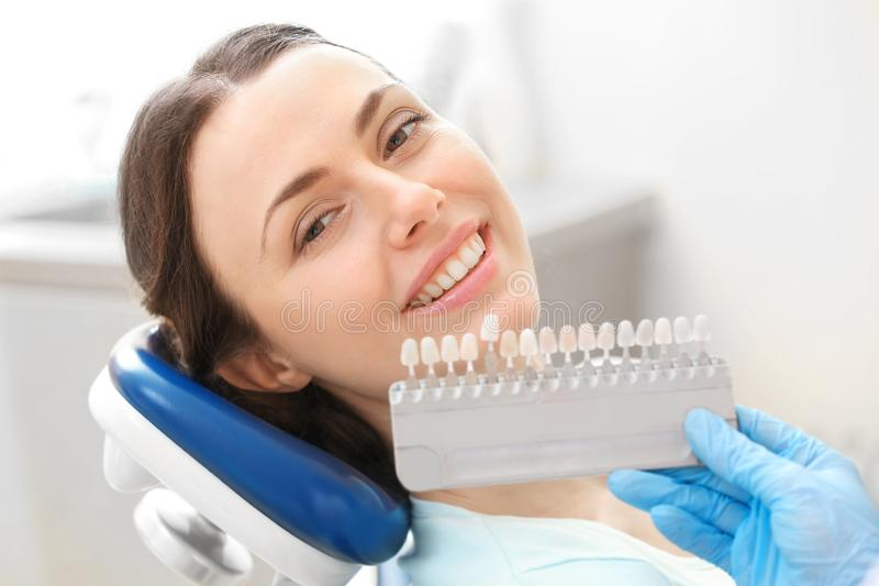 Dentist checking and selecting color of young woman`s teeth royalty free stock photo