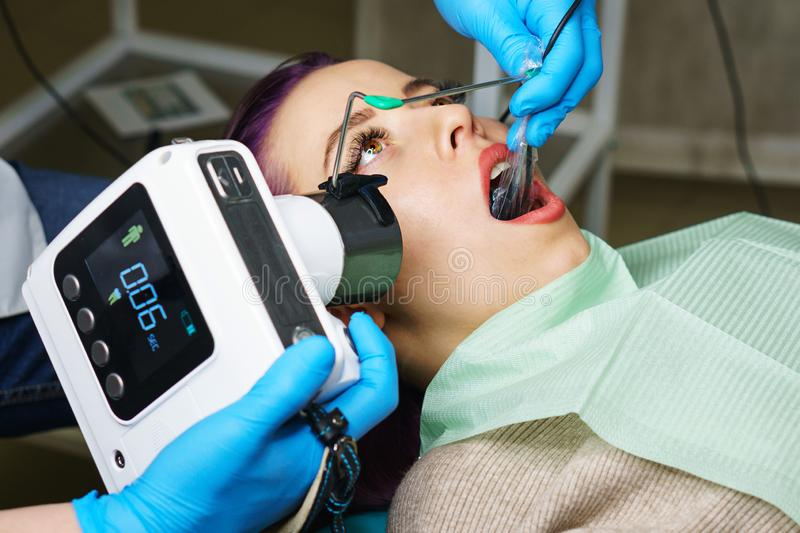 Dentist with portable x-ray. Dentist checks thickness of tooth enamel using portable x-ray. Young girl with open mouth. White teeth. Dentist hands closeup royalty free stock image