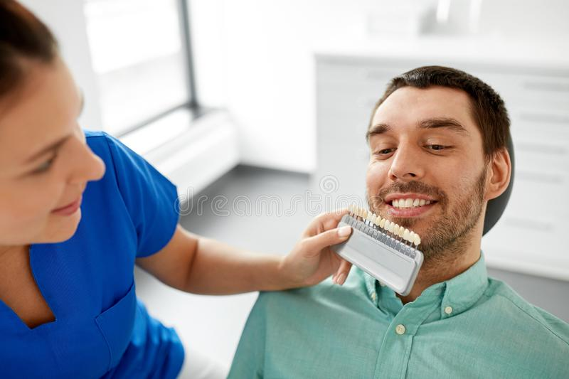 Dentist choosing tooth color for patient at clinic royalty free stock images