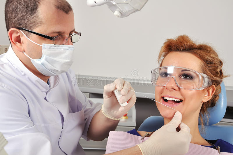 Dentist cleans teeth stock image