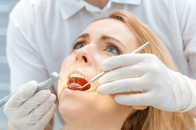 Dentist curing scared patient looking up royalty free stock photography