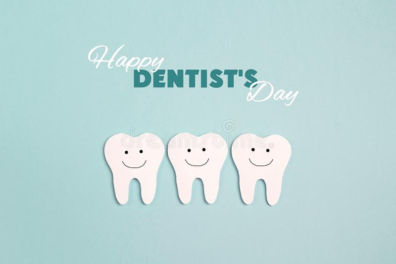 Dentist day concept with white paper teeth on blue background royalty free stock photo