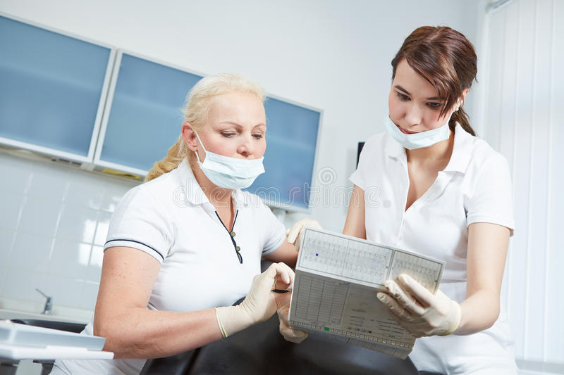 Dentist and dental assistant reading medical recor. Ds of a patient prior to treatment royalty free stock image