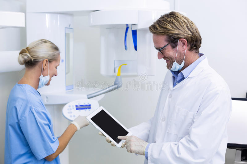 Dentist and dental assistant working on digital tablet. In dental clinic royalty free stock photos