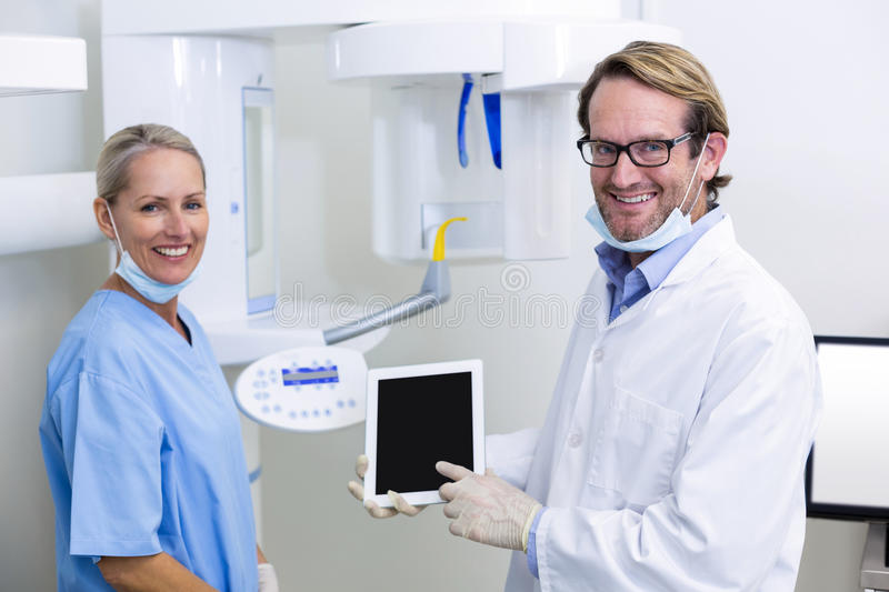 Dentist and dental assistant working on digital tablet. Portrait of dentist and dental assistant working on digital tablet in dental clinic stock images