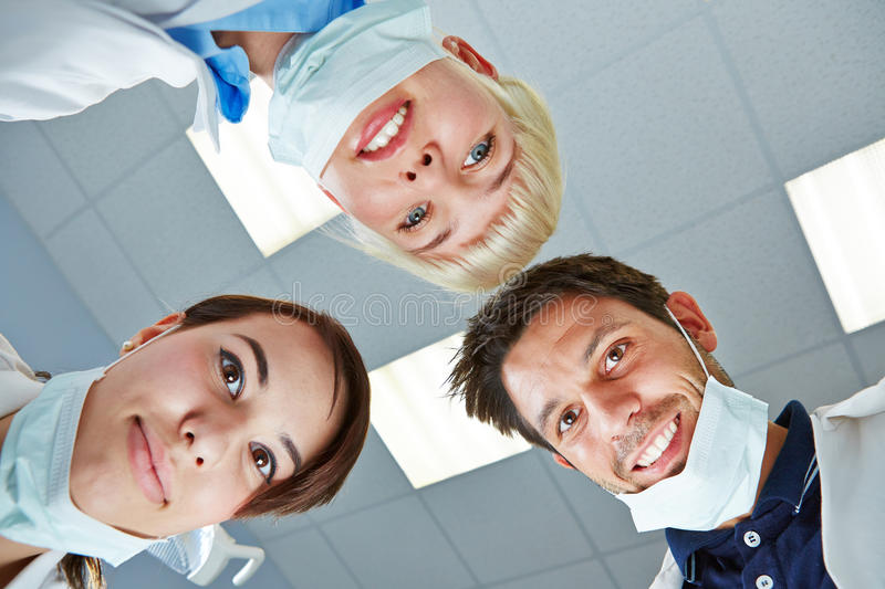 Dentist and dental team looking down stock photo