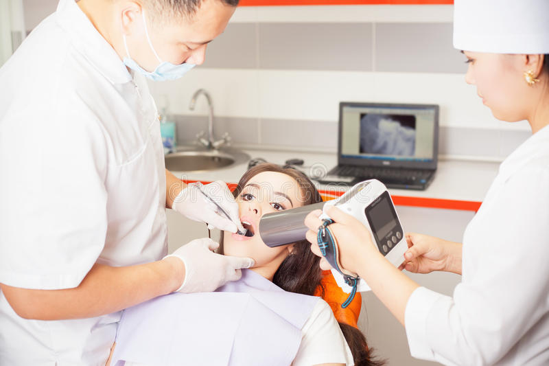Dentist doctor doing dental treatment and using x-ray computer stock images