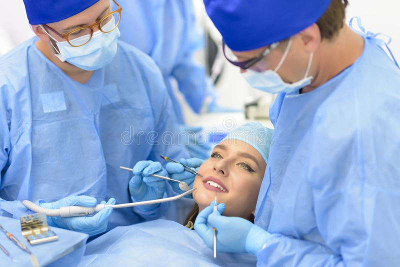 Dentist Doctor and his Team Treating a Patient royalty free stock image