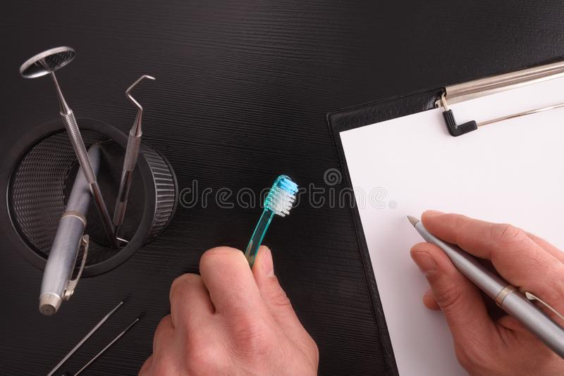 Dentist doctor with toothbrush writing on his desk top view royalty free stock image