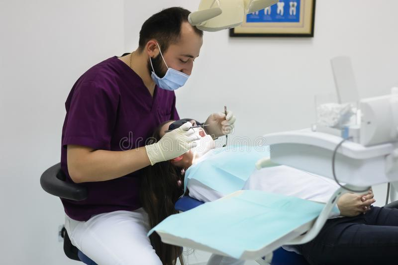 Dentist examines a  woman patient working explaining   healthy. Dentist examines a  women patient working explaining   healthy check stock photo
