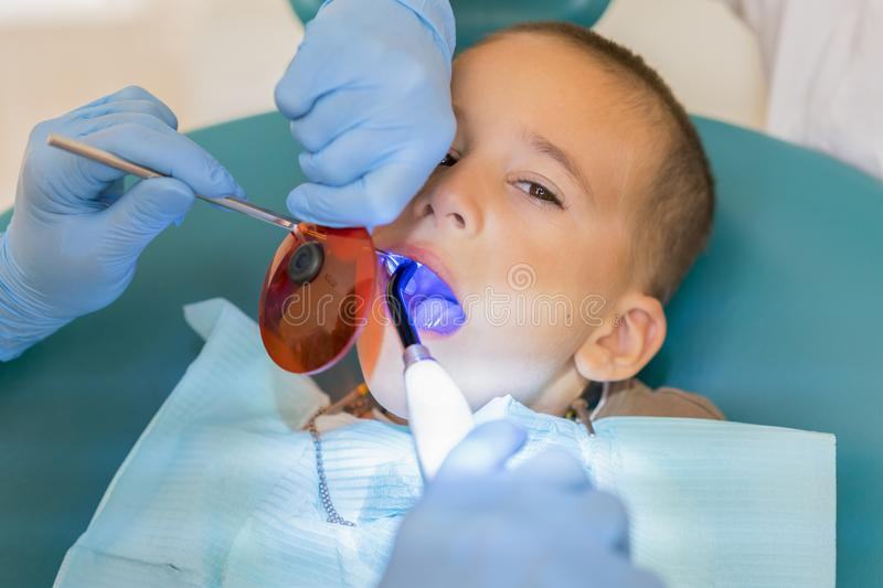 Dentist examining boy's teeth in clinic. A small patient in the dental chair smiles. Dantist treats teeth. close up view of. Dentist examining boy`s teeth in royalty free stock photography