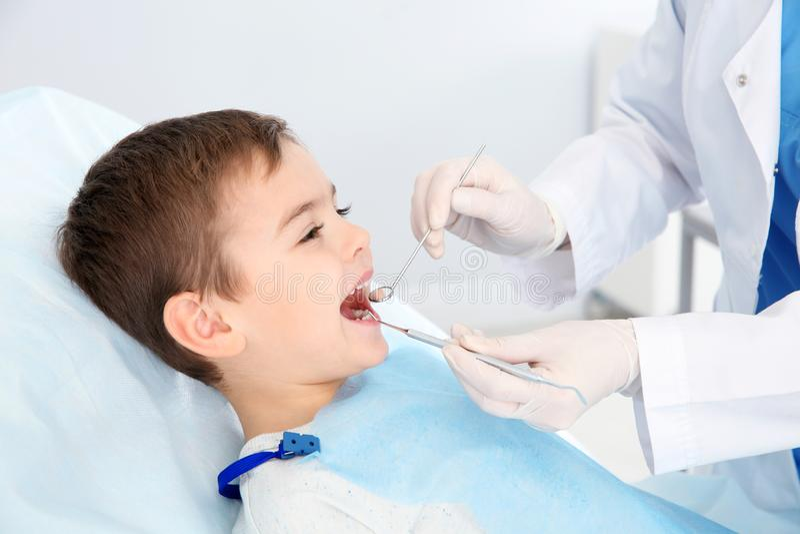Dentist examining cute boy`s teeth royalty free stock photos
