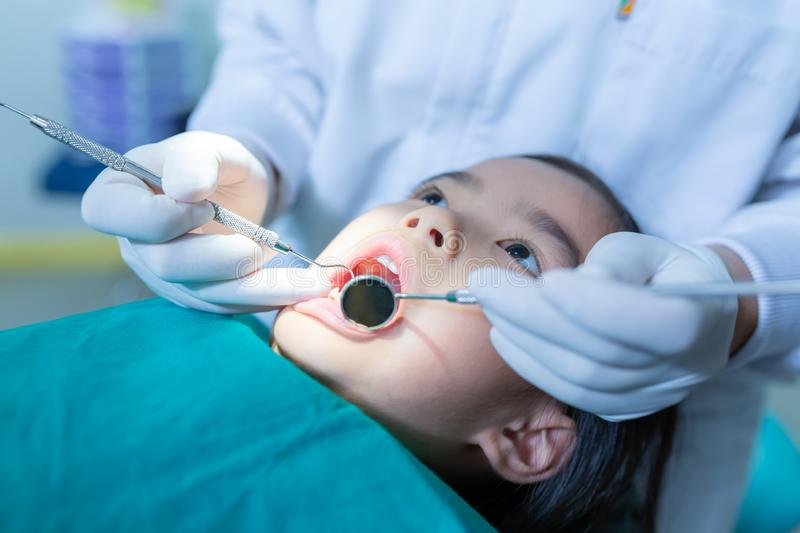 Dentist examining little girl`s teeth in clinic. royalty free stock image