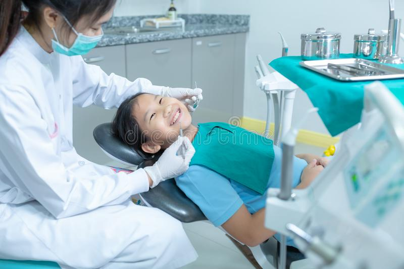 Dentist examining little girl`s teeth in clinic. royalty free stock photo
