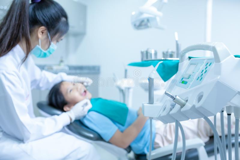 Dentist examining little girl `s teeth in clinic. stock images