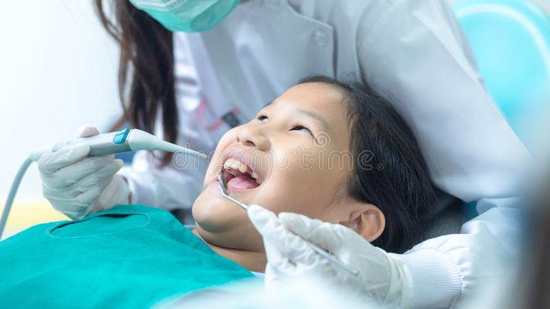 Dentist examining little girl`s teeth in clinic. stock photography