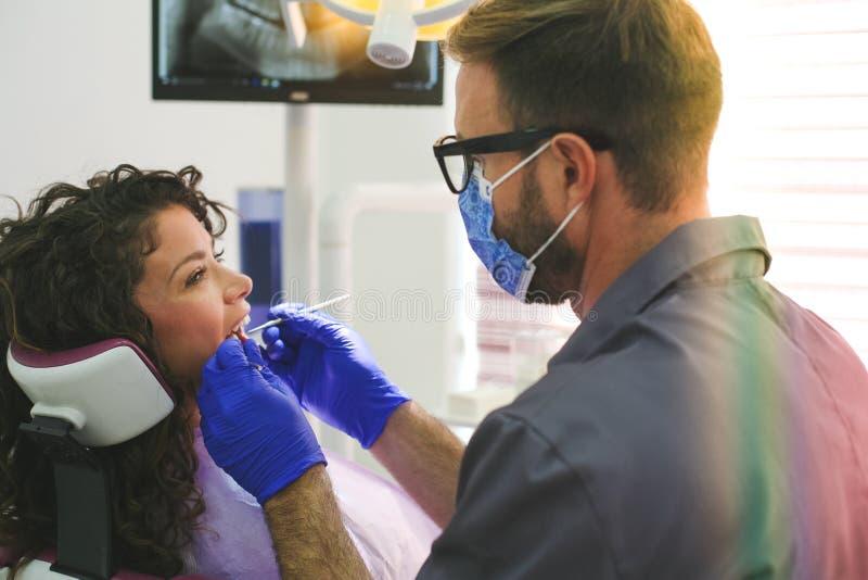 Dentist examining patient`s teeth. Male dentist. royalty free stock photos