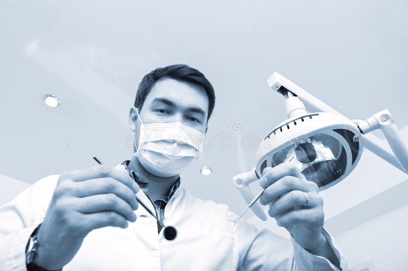 Dentist examining a patients teeth in the dentists chair stock image