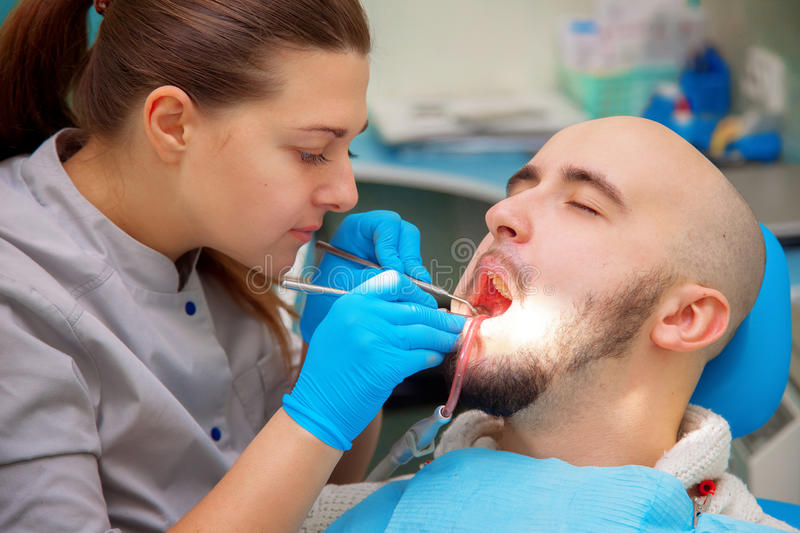 Dentist examining a patients teeth in the dentists chair under b royalty free stock images