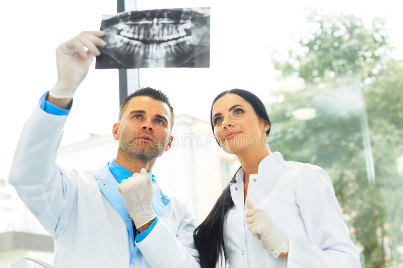 Dentist and female assistant are discussing dental X Ray image.  royalty free stock photos