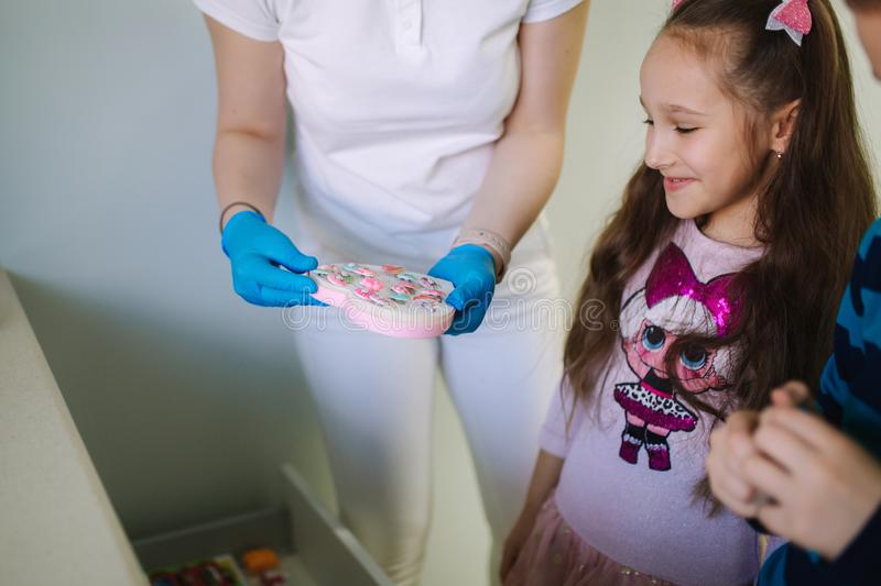Dentist give a toy for little patient, happy children get a present stock photo