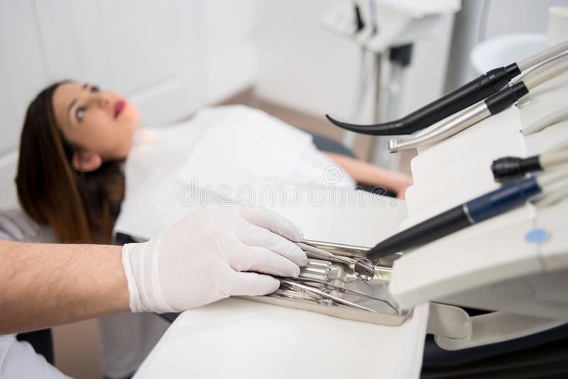 Dentist with gloved hands is treating patient with dental tools in dental hospital. Dentistry. Selective focus on the tools royalty free stock images