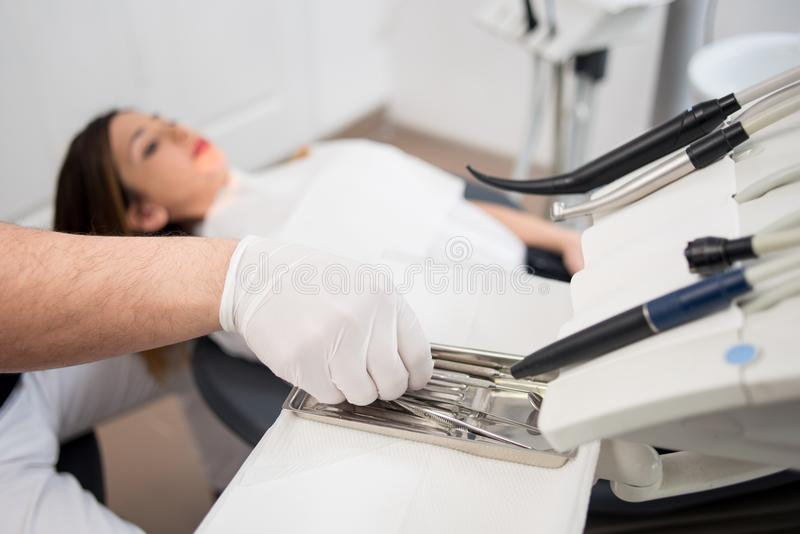 Dentist with gloved hands is treating patient with dental tools in dental office. Dentistry. Selective focus on the tools royalty free stock photo