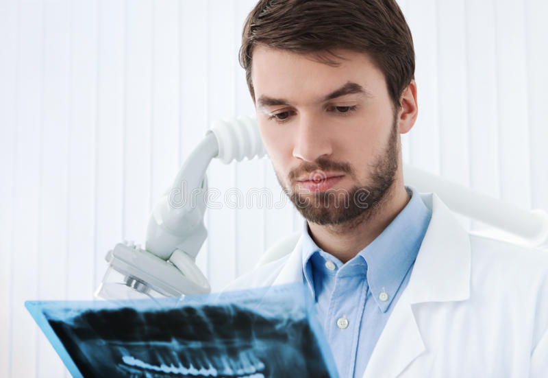 Dentist goes deep into details of roentgenogram. Dentist goes deep into details of the roentgenogram, whte background royalty free stock photo