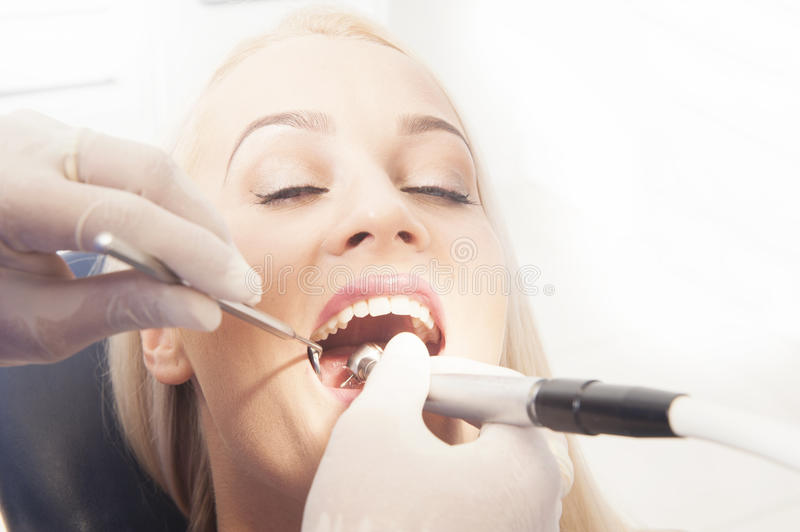 Dentist hands working with female teeth stock photos