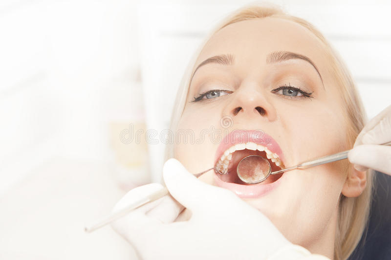 Dentist hands working with female teeth. Close up of Dentist hands working with attractive female teeth royalty free stock image