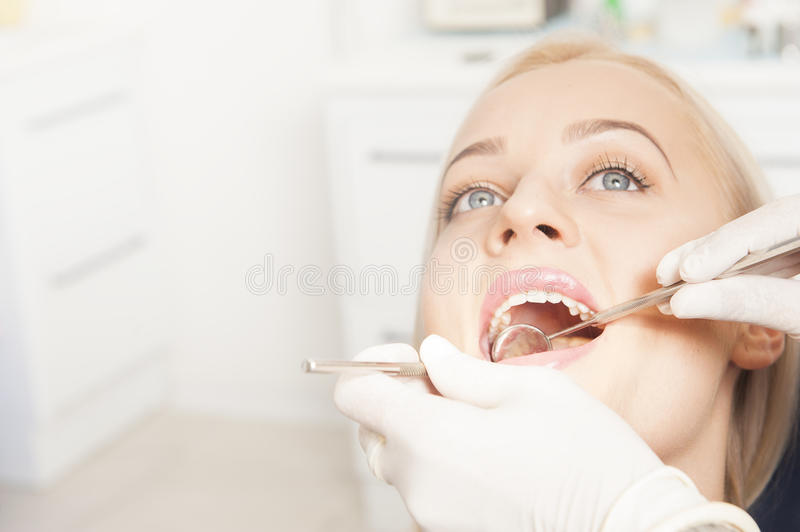Dentist hands working with female teeth. Close up of Dentist hands working with attractive female teeth royalty free stock photography