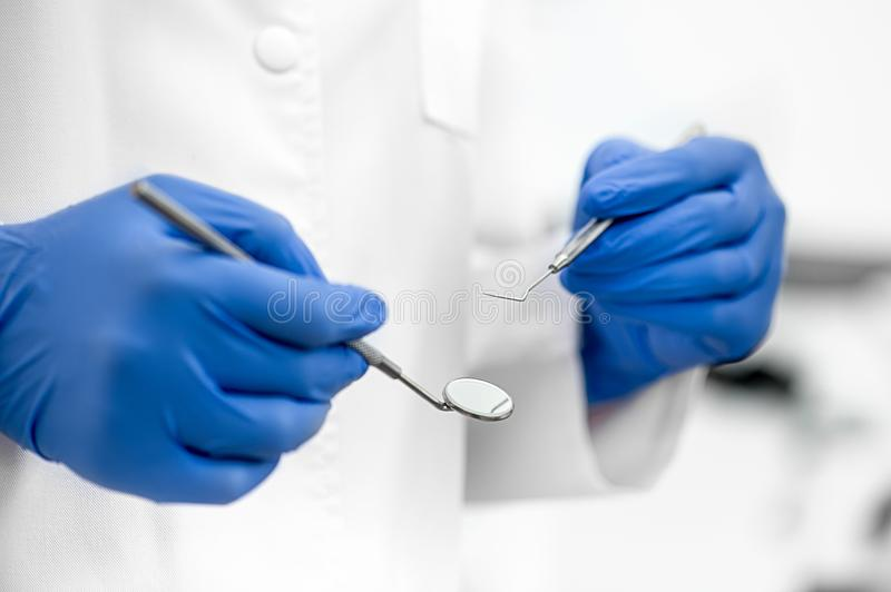 Dentist holding dental tools. With blue gloves stock photography