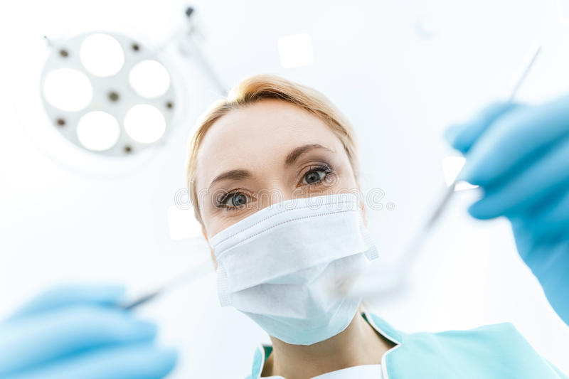 Dentist in medical mask working in clinic and looking at camera. Professional dentist in medical mask working in clinic and looking at camera stock images