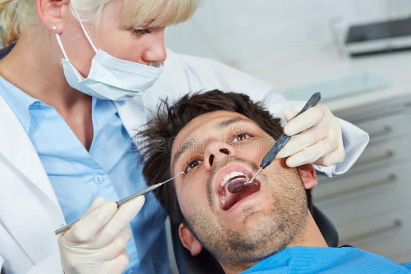 Dentist with mirror and probe. Dentist examining mouth of patient with mirror and probe stock photos