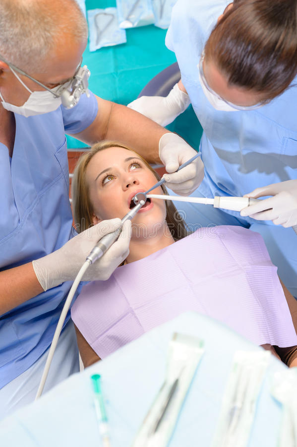 Dentist With Nurse Doing Procedure On Patient Royalty Free Stock Image