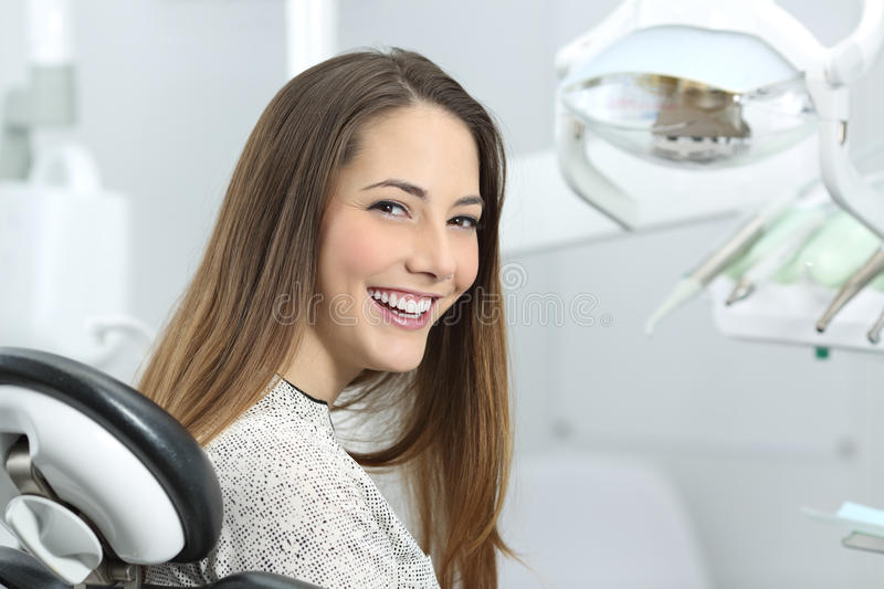 Dentist patient showing perfect smile after treatment. Satisfied dentist patient showing her perfect smile after treatment in a clinic box with medical equipment