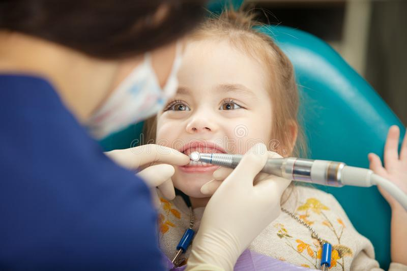 Dentist polishes childs teeth with modern electric tool royalty free stock image