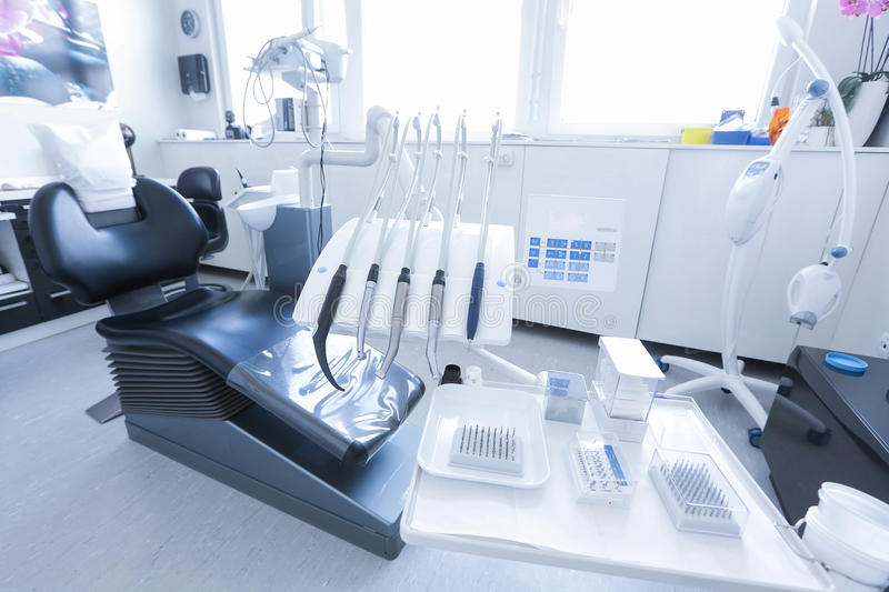 Dentist's chair with tools and drills. Dentists office with chair, tools and drills in the foreground. Dental care, dental hygiene, checkup and therapy concept stock photography