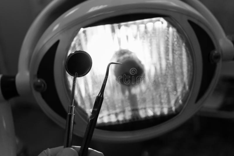 In the dentist`s office - fear and distrust of the patient before dental treatment. Black and white image. In the dentist`s office - a dental mirror and a probe royalty free stock photo