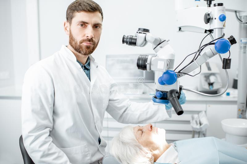 Dentist`s portrait with a microscope stock images