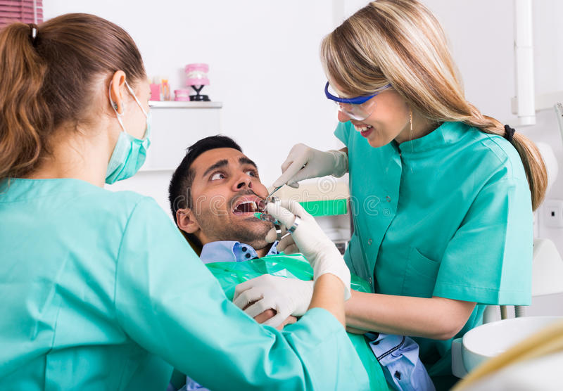 Dentist and scared patient. Female dentist with assistant and scared male patient during check up at clinic royalty free stock image