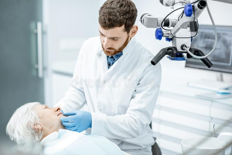 Dentist with senior woman patient in the surgery dental office stock images