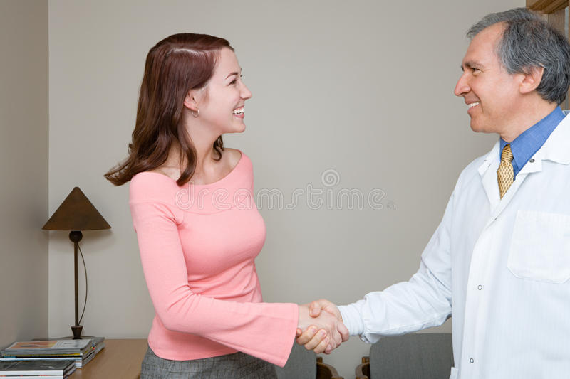 Dentist shaking hands with patient royalty free stock images