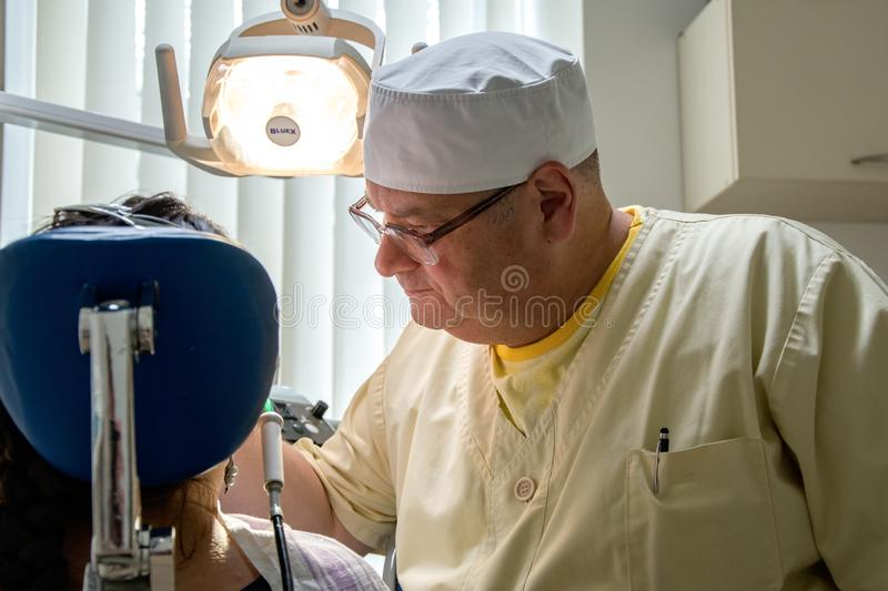 The dentist shines a UV light seal to a woman in a private clinic. 2 stock photos