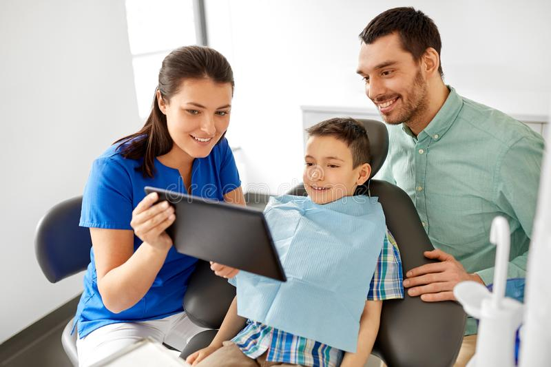 Dentist showing tablet pc to kid at dental clinic stock image