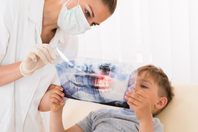 Dentist Showing Teeth Xray To Child Patient stock photos